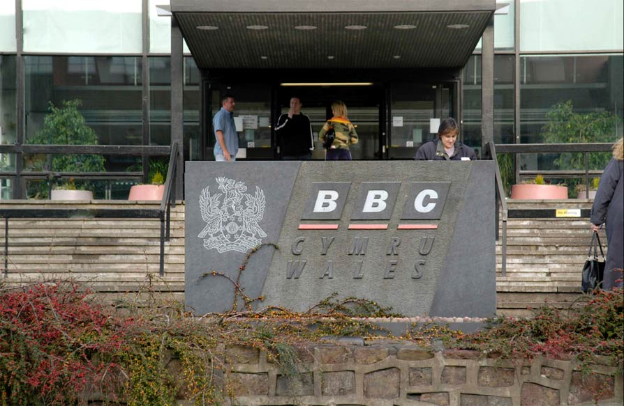 Sign for BBC Wales using sans serif font and coat of arms detail.
